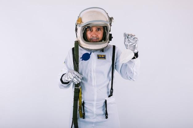 Cosmonauta maschio in tuta spaziale e casco, in possesso di una maschera fpp2, su sfondo bianco. covid-19 e concetto di virus