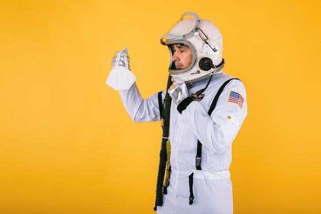 Cosmonauta maschio in tuta spaziale e casco, con in mano una maschera fpp2, sulla parete gialla. covid19 e il concetto di virus