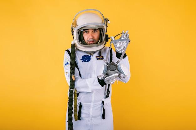 Cosmonauta maschio in tuta spaziale e casco, che tiene una maschera, sulla parete gialla. covid19 e il concetto di virus