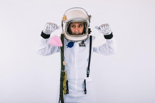 Cosmonauta maschio in tuta spaziale e casco, con in mano due maschere fpp2, su sfondo bianco. covid-19 e concetto di virus