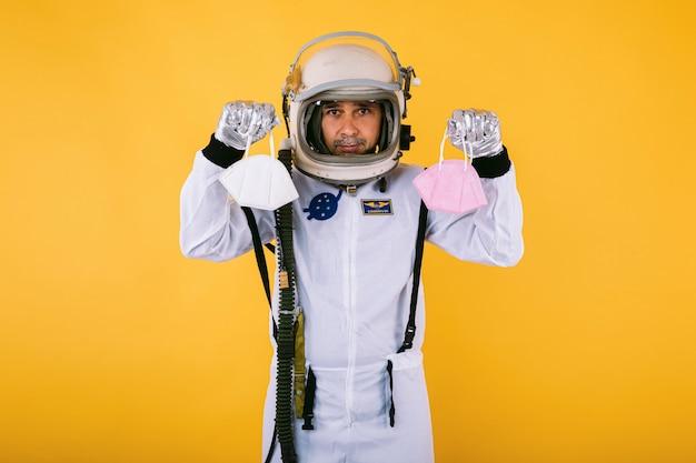 Cosmonauta maschio in tuta spaziale e casco, con in mano due maschere fpp2, sulla parete gialla. covid19 e il concetto di virus