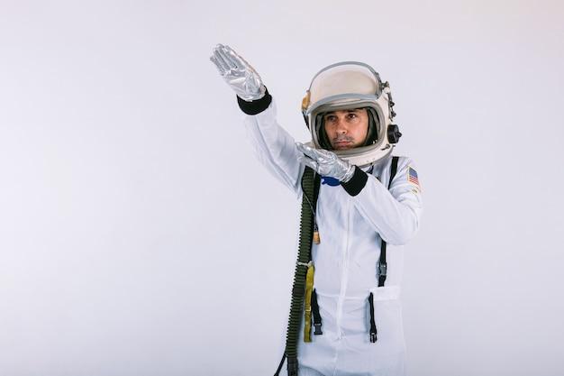 Cosmonauta maschio in tuta spaziale e casco, puntando il dito verso il cielo, su sfondo bianco.