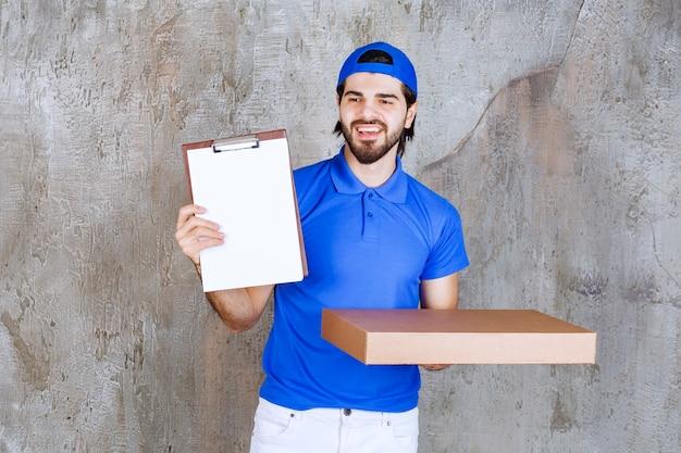 Corriere maschio in uniforme blu che trasporta una scatola di cartone e presenta l'elenco delle firme.