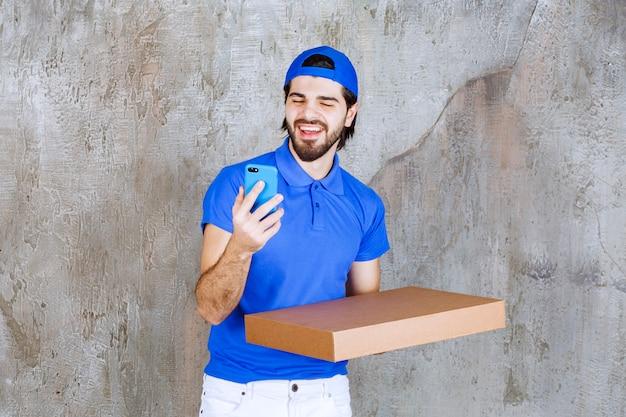 Corriere maschio in uniforme blu che trasporta una scatola di cartone e prende nuovi ordini via telefono.
