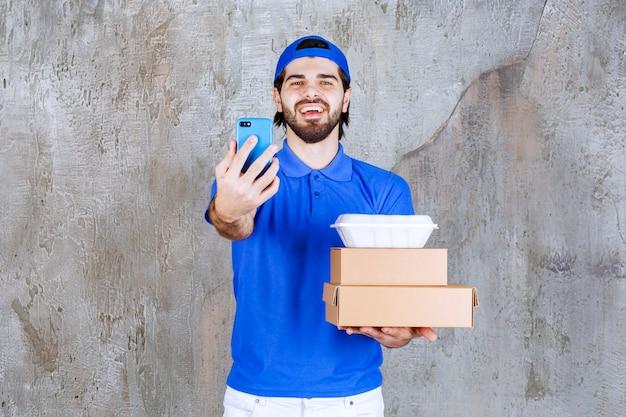 Corriere maschio in uniforme blu che trasporta scatole di cartone e plastica e prende nuovi ordini tramite smartphone.