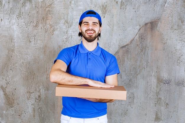 Corriere maschio in uniforme blu che trasporta una scatola di cartone da asporto.