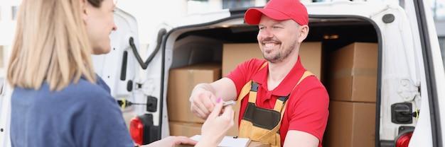 Il corriere maschio dà al cliente la ricevuta per ricevere il pacco