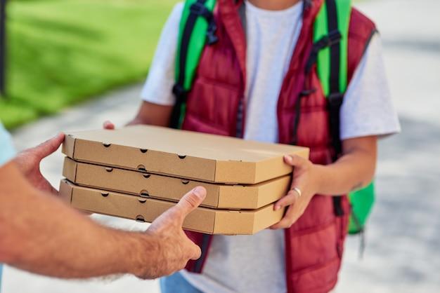 Corriere maschio che dà scatole con pizza al cliente mentre si trova in una strada soleggiata