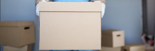 Il corriere maschio tiene in mano una grande scatola di cartone