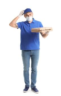 Corriere maschio in mascherina medica e con pizza su superficie bianca