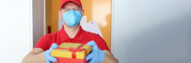 Il corriere maschio in maschera protettiva e guanti consegna una confezione regalo
