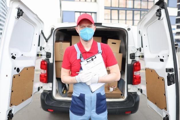 Il corriere maschio in maschera medica protettiva consegna i pacchi