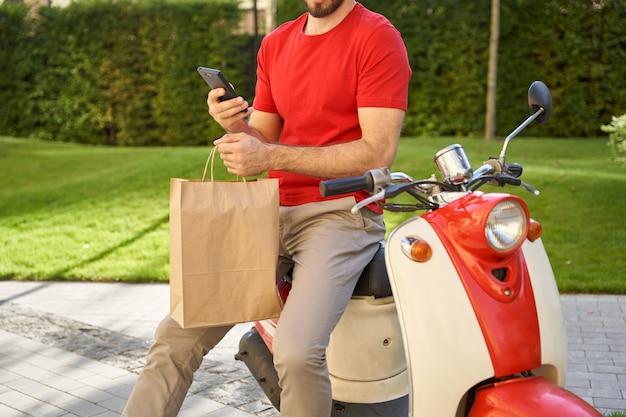 Corriere maschio che utilizza l'app mobile durante la consegna della borsa ecologica di carta con