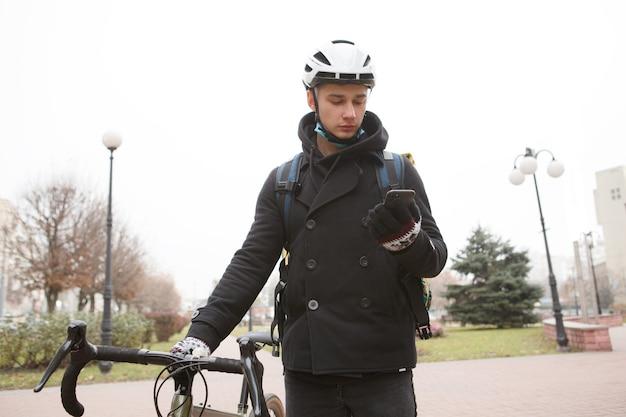 Corriere maschio utilizzando smart phone a piedi con la sua bicicletta in città