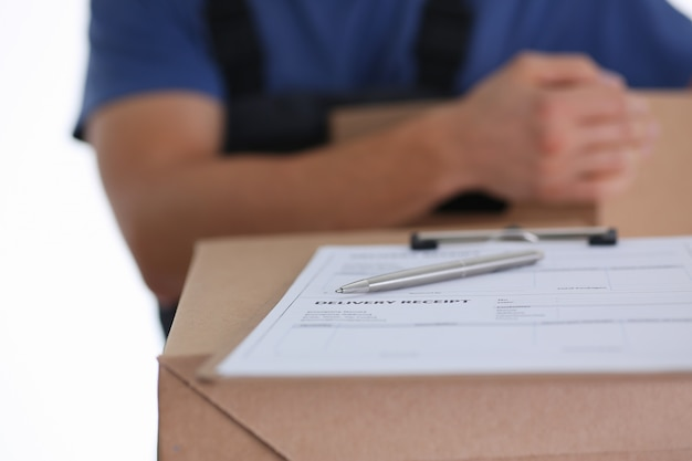 Corriere maschio che aspetta il segno del cliente mentre consegnando pacco