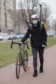 Corriere maschio che indossa una maschera medica, cammina con la sua bicicletta, portando lo zaino termico