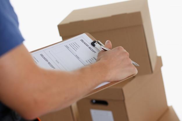 Corriere maschio con appunti in piedi vicino a scatole di cartone