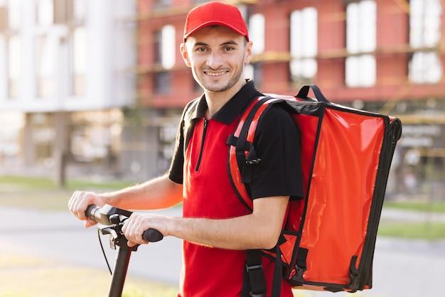 Corriere maschio con zaino rosso e scooter elettrico che consegna un ritratto di trasporto verde