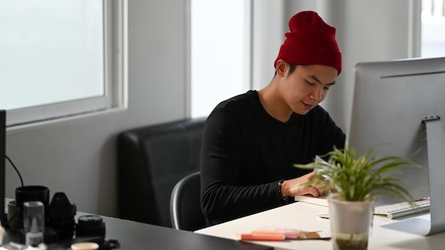 Un designer grafico creativo maschio sta leggendo un libro mentre è seduto davanti al computer sul posto di lavoro.