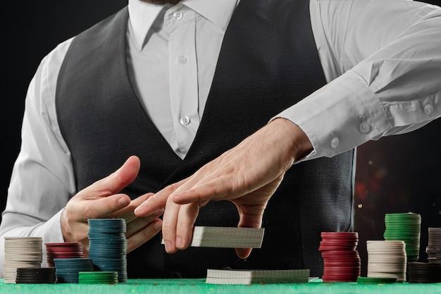 Il croupier maschio nel casinò al tavolo passa il primo piano. concetto di casinò, gioco d'azzardo, poker, fiches sul tavolo del casinò verde.