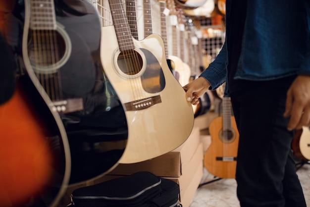 Cliente maschio che sceglie la chitarra acustica nel negozio di musica. assortimento nel negozio di strumenti musicali, attrezzatura per l'acquisto di musicisti