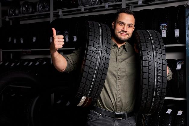 Il cliente maschio è soddisfatto dell'acquisto di pneumatici nel garage di riparazione automobilistica, in piedi tenendo in mano la gomma per auto, nel negozio di auto