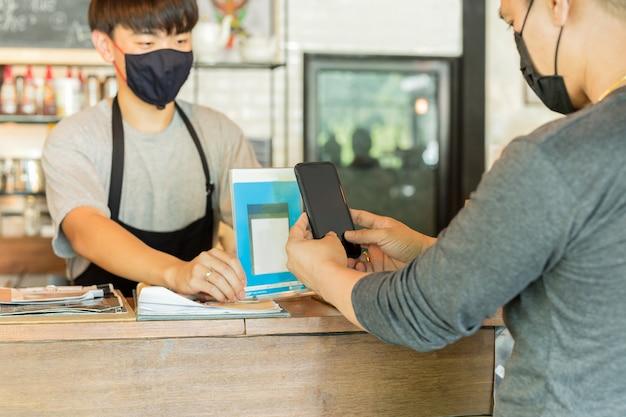 Cliente maschio con la maschera protettiva che paga fattura dal telefono cellulare in caffè.