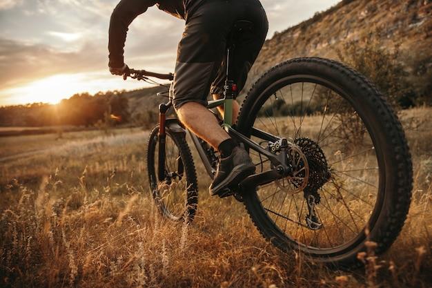 Ciclista maschio in sella a bici nella valle erbosa vicino alle montagne