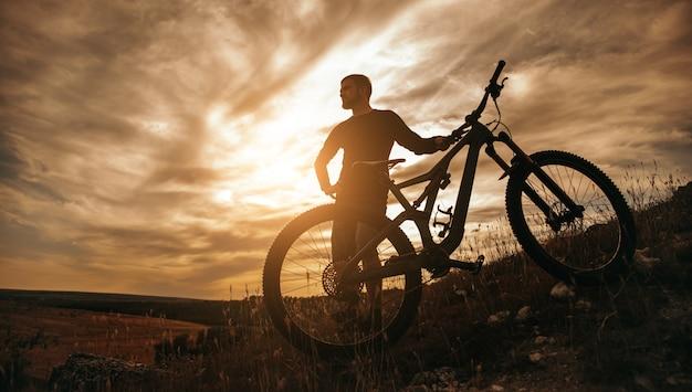 Ciclista maschio in piedi con la bici sul pendio della collina