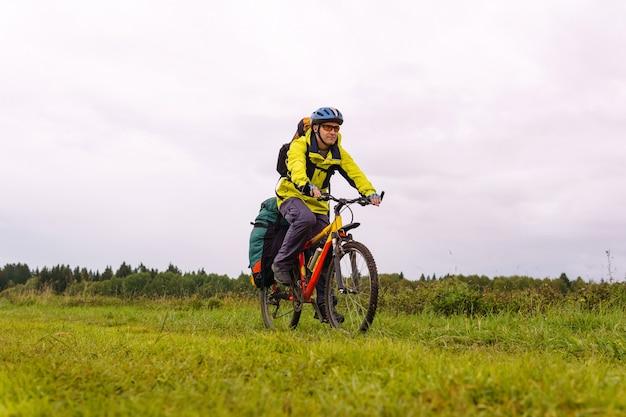 Il viaggiatore ciclista maschio con uno zaino e una borsa a cremagliera attraversa il paesaggio naturale