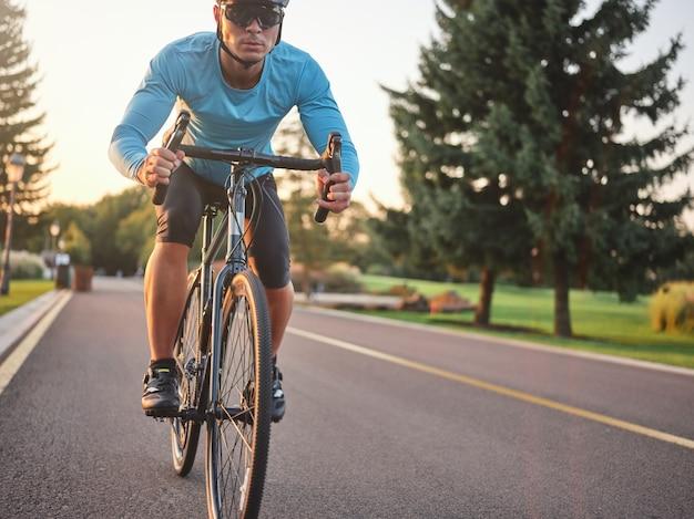 Ciclista maschio che indossa un casco protettivo di abbigliamento sportivo e occhiali che sembrano concentrati mentre guidano una bicicletta