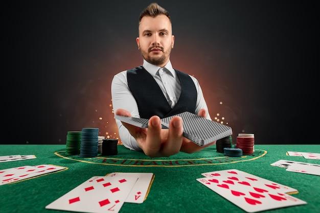 Mazziere al casinò al tavolo. concetto di casinò, gioco d'azzardo, poker, fiches sul tavolo del casinò verde.
