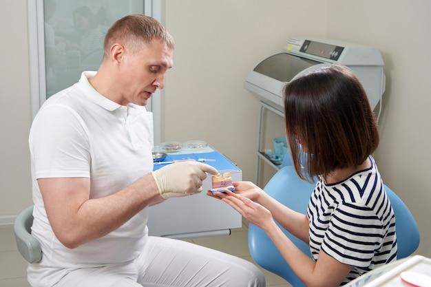 Dentista maschio che mostra al suo paziente femminile un impianto dentale