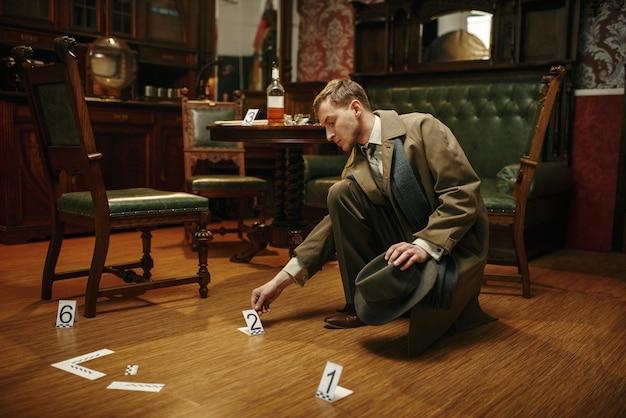 Detective maschio in cappotto che raccoglie prove sulla scena del crimine, in stile retrò. indagine penale, ispettore sta lavorando a un omicidio, interni di una stanza vintage