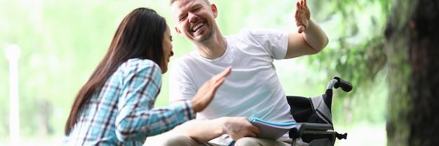 Uomo disabile maschio con la ragazza che sorride sul ritratto della passeggiata del parco. concetto di adattamento di disabilità sociale