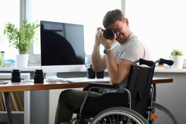 Il fotografo disabile maschio tiene la macchina fotografica in sue mani
