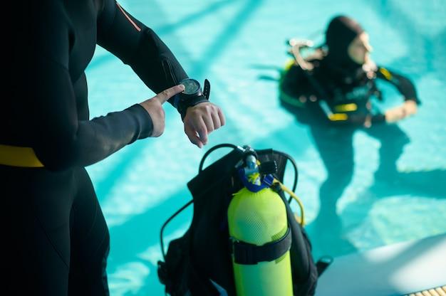 Subacqueo maschio e divemaster in attrezzatura subacquea segnano il tempo di immersione, scuola di immersioni. insegnare alle persone a nuotare sott'acqua, interno della piscina coperta sullo sfondo