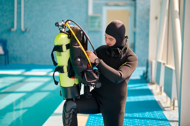 Il subacqueo maschio in attrezzatura subacquea mette su bombola di ossigeno, scuola di immersioni. insegnare alle persone a nuotare sott'acqua, interno della piscina coperta sullo sfondo