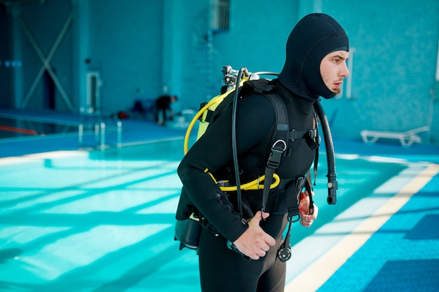 Il subacqueo maschio in muta si prepara per l'immersione, la scuola di immersioni. insegnare alle persone a nuotare sott'acqua, interno della piscina coperta sullo sfondo
