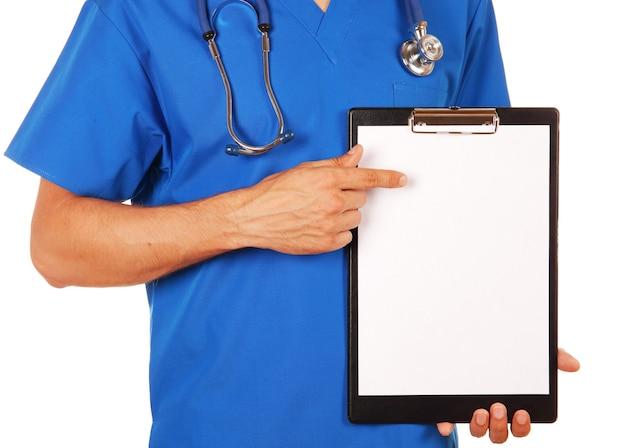 Medico maschio in uniforme blu con lo stetoscopio che mostra la lavagna per appunti in bianco per scriverlo sul vostro messaggio o consiglio personale