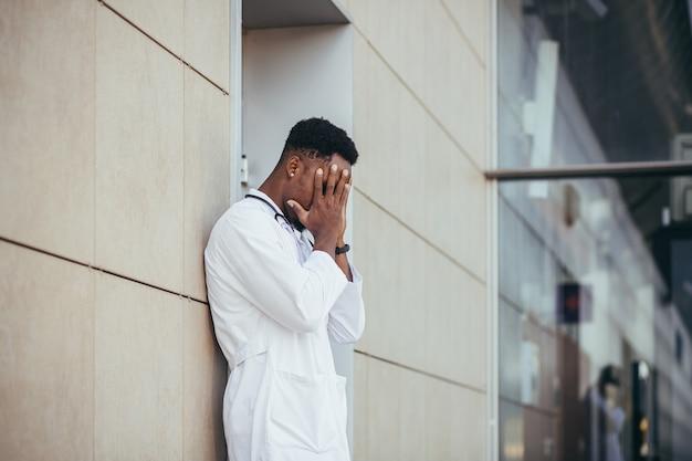 Il medico maschio della clinica che si tiene la testa ha problemi di salute e stanco dopo una dura giornata, depresso non ha ottenuto il risultato desiderato, il medico afroamericano è triste