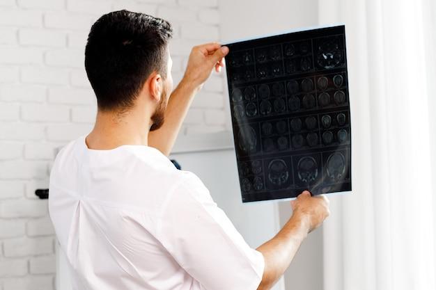 Il medico maschio esamina la risonanza magnetica cerebrale di un paziente