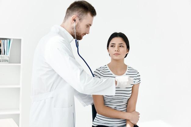 Il medico maschio esamina il paziente in salute ospedaliera