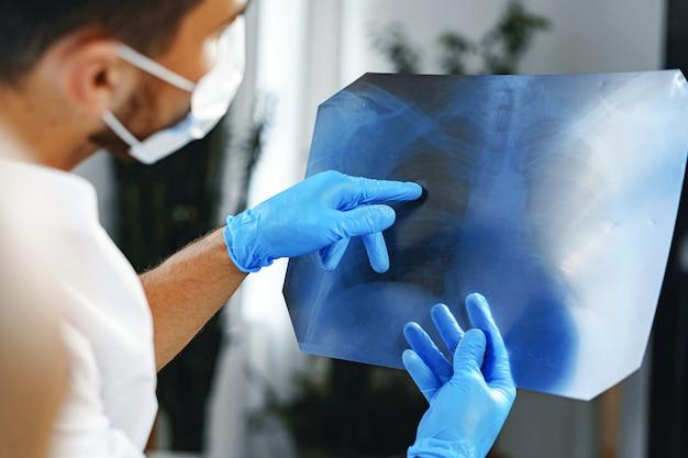 Il medico maschio esamina una radiografia dei polmoni in ospedale