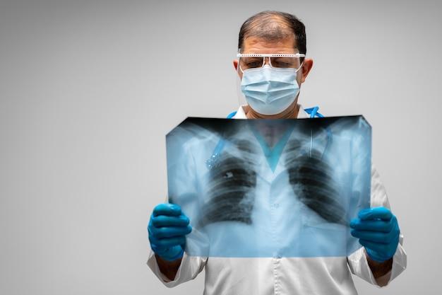 Medico maschio che esamina la scansione a raggi x dei polmoni contro il grigio si chiuda