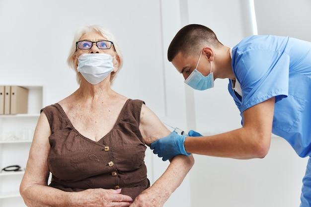 Medico maschio che dà un passaporto del vaccino per iniezione in maschere mediche
