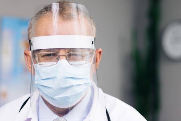 Medico maschio con gli occhiali che indossa una maschera protettiva trasparente per il viso e una tuta in una stanza d'ospedale al covid19