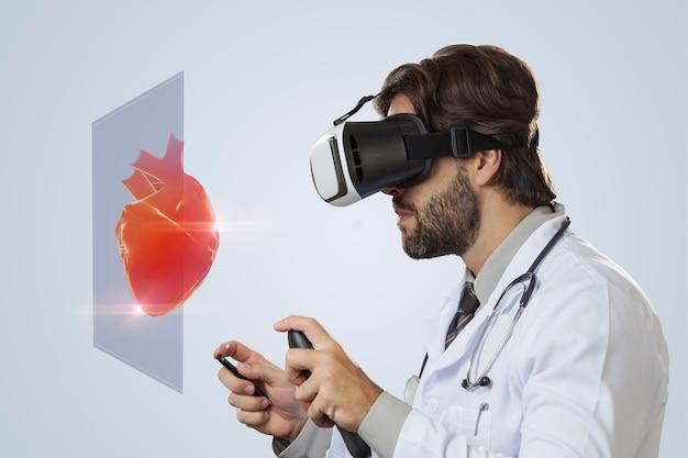 Medico maschio su un muro grigio utilizzando occhiali per realtà virtuale, guardando un cuore virtuale