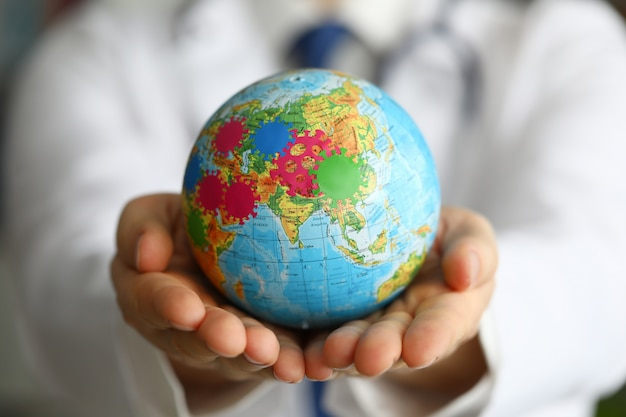 Terra maschio della stretta della mano del medico con il primo piano di simbolo del virus.