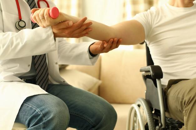 Medico maschio aiuta a sollevare il manubrio al concetto di terapia di riabilitazione del paziente disabile.